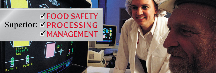 Dairy Processing image of 2 adults in food safety attire with computer screen